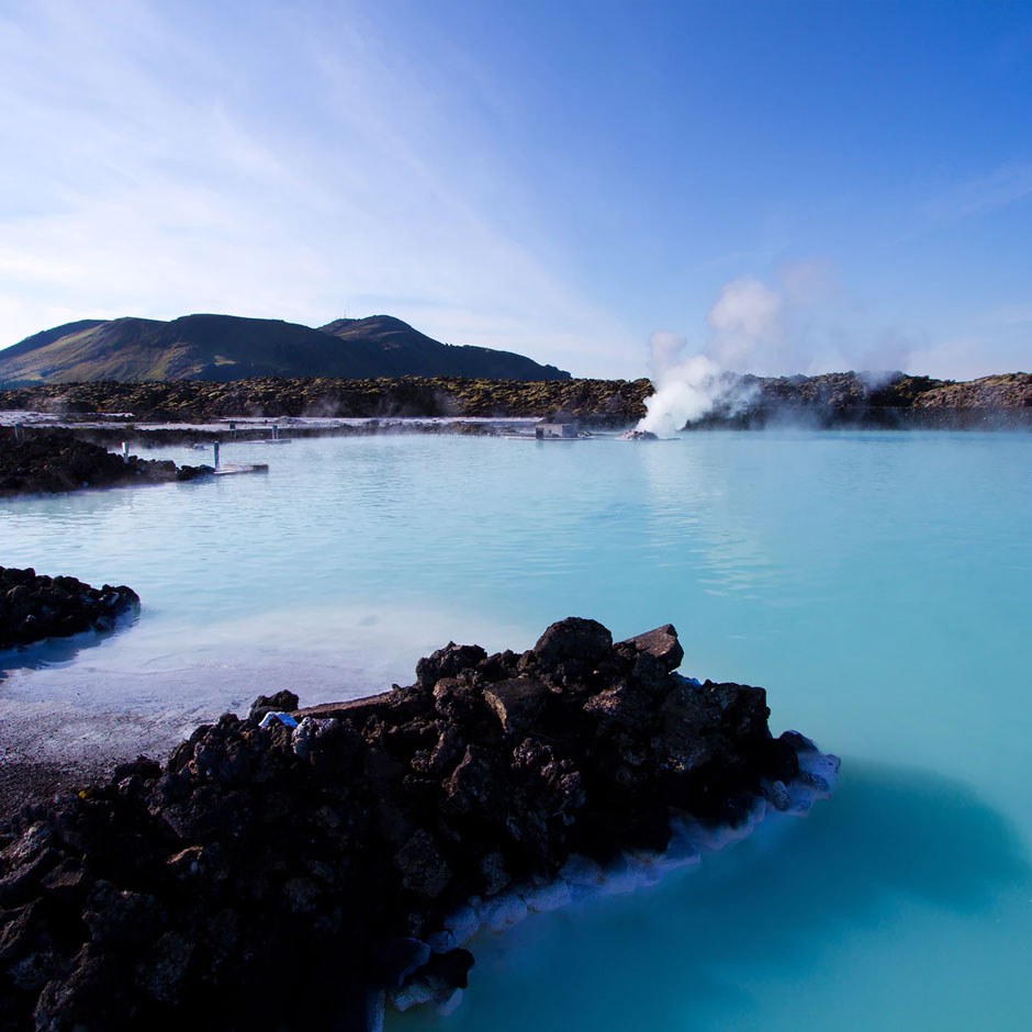 Blue waters and steam of the Blue Lagoon in iceland with mountains in the background
