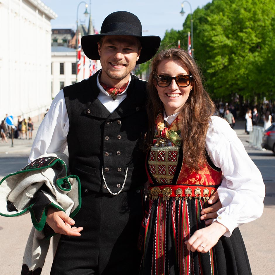 A young man and woman wear traditional Norwegian dress. He wears a black waistcoat, hat and trousers. She wears a highly embroidered and decorated red dress