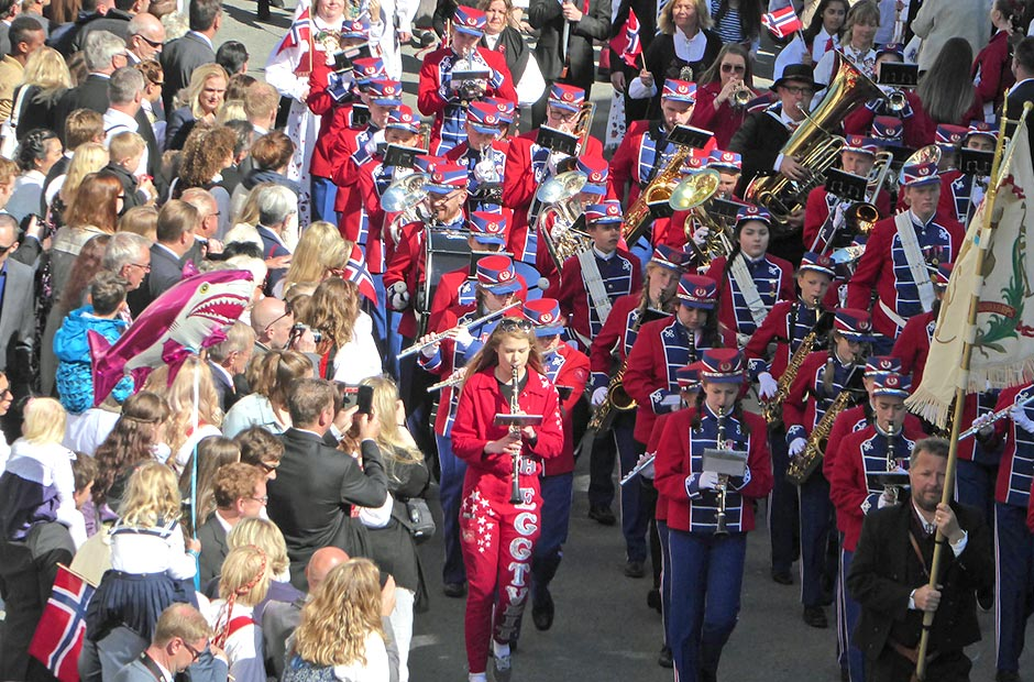 Children playing instruments lead a colourful parade down the street as cheering crowds stand either side of the road