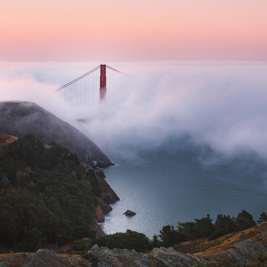 Part of the Golden Gate Bridge visible through a thick fog and a pink sky in the background as seen from a nearby mountain