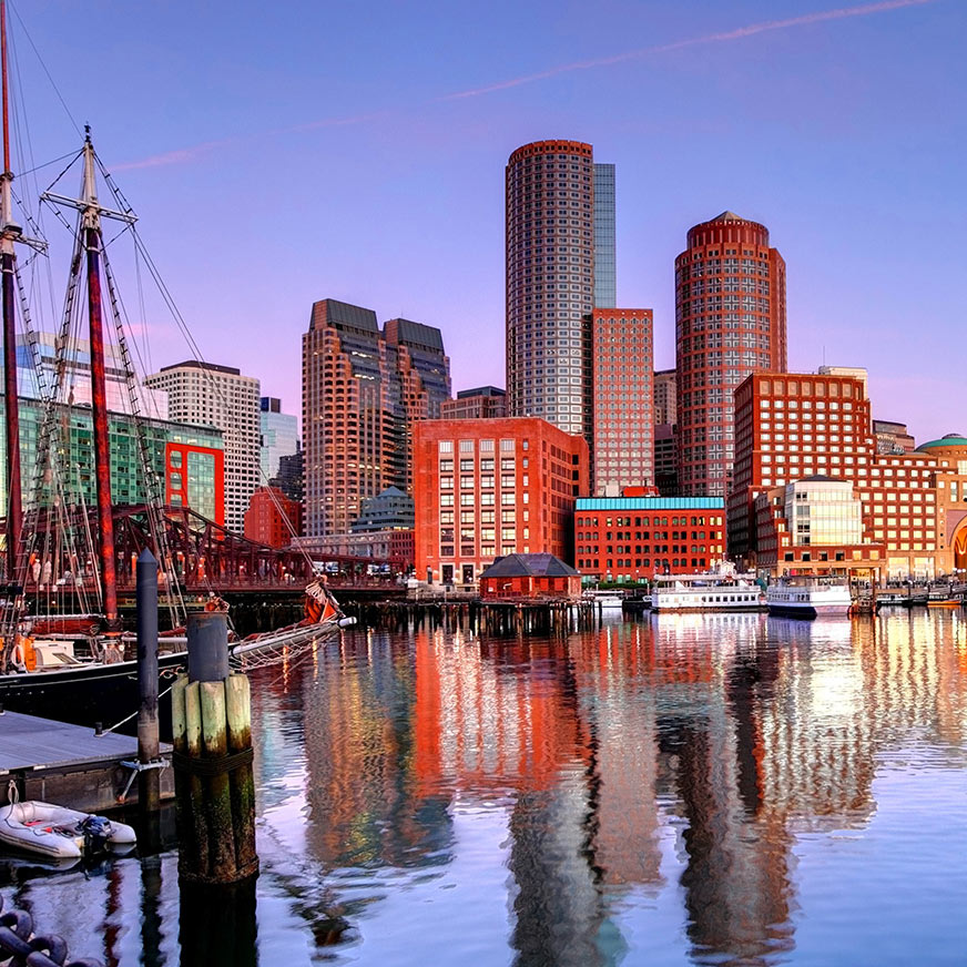 Boston buildings and harbour against a blue-purple sky