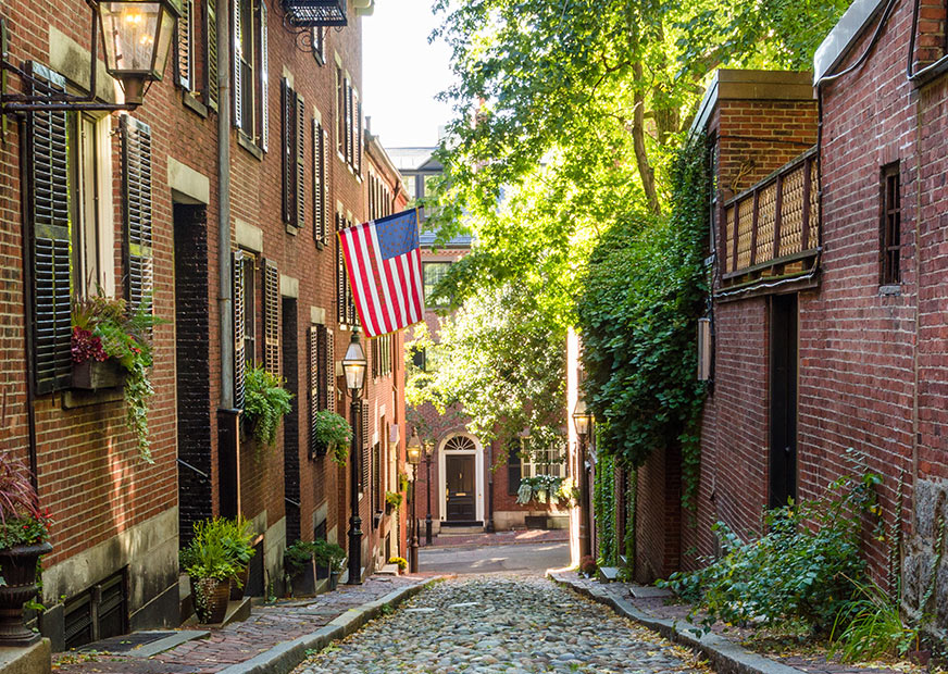 Cobbled street in Boston with houses on either side and trees