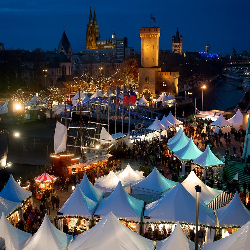 Stalls, people and ship at the Cologne Harbour Christmas Market at night with the cathedral in the background