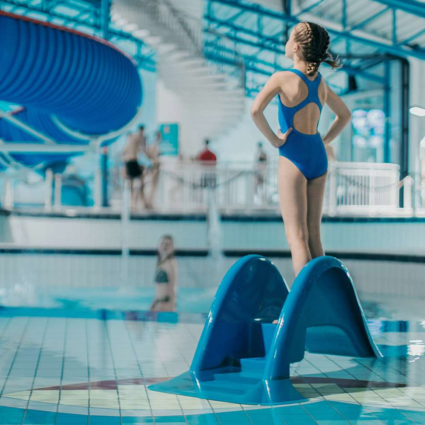 Girl stands on steps of a slide looking towards the pool at Vannkanten Waterworld.