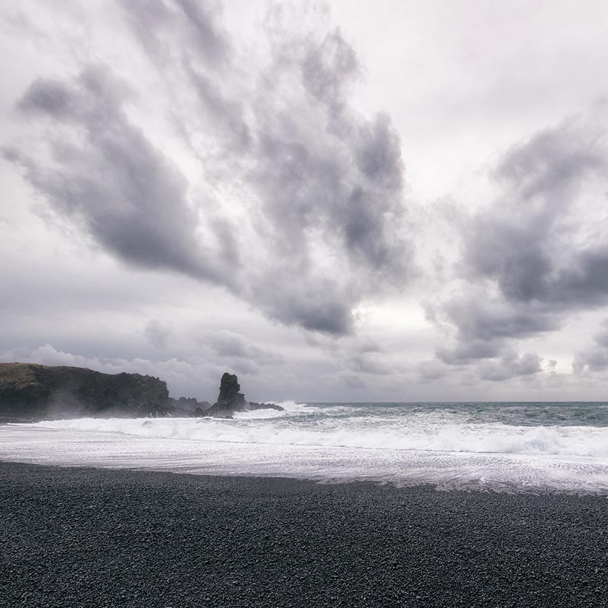 Grey skies over a black-sand beach and crashing waves