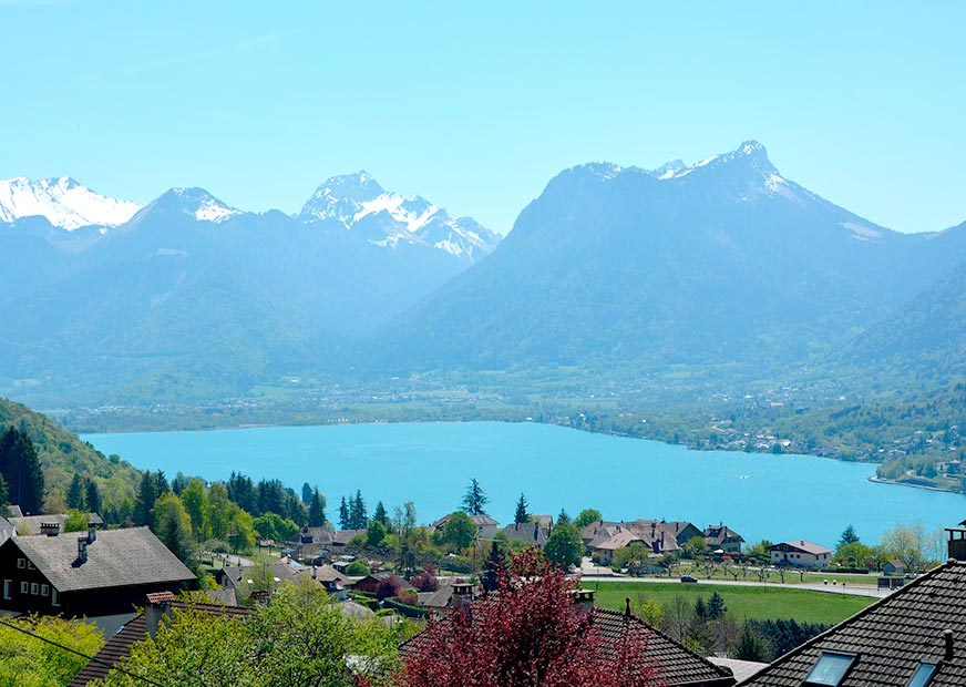 The blue Lake Annecy with a town in the foreground and snow-capped mountains in the background