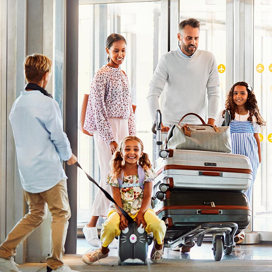 Family with three children wheel luggage at an airport