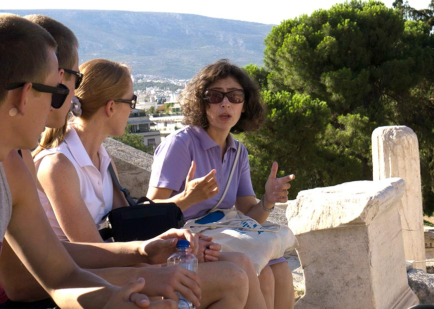 A female tour guide sitting on a wall in Greece explaining something to three tourists