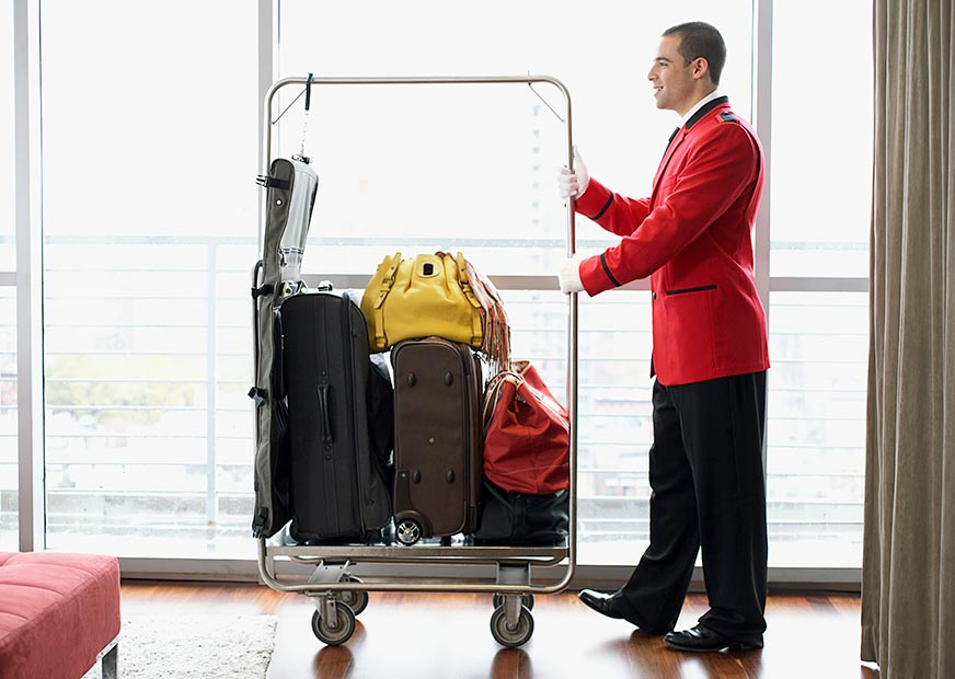 A hotel porter delivers bags and suitcases on a trolley in a hotel room
