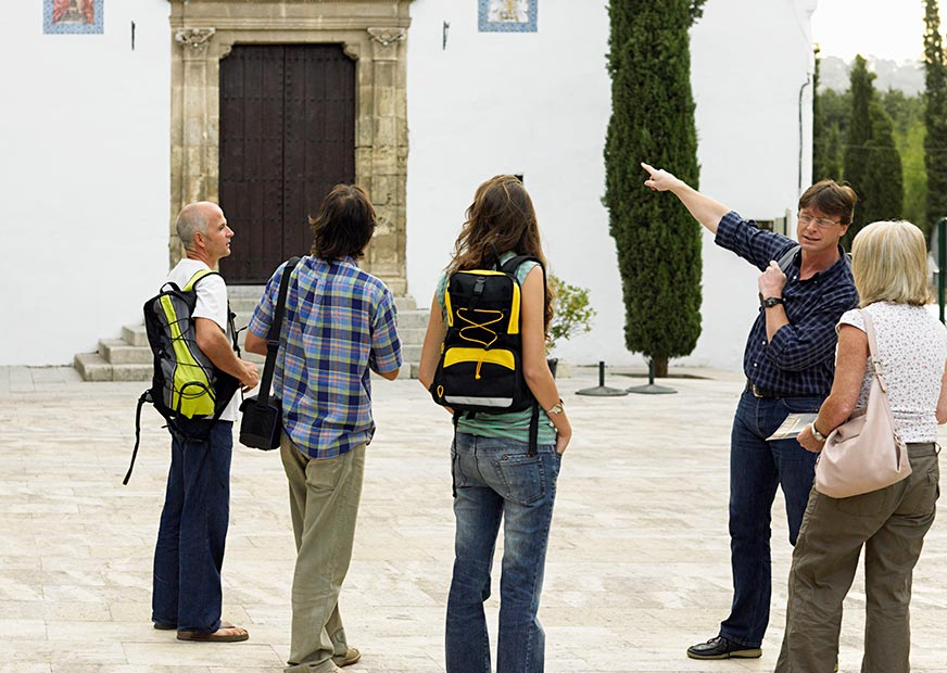 A tour guide points to a building in Spain while talking to a group of four tourists
