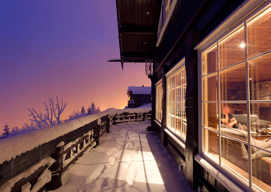 Side of a snow-covered cabin with sunset in the background and a glimpse into the living room through the window