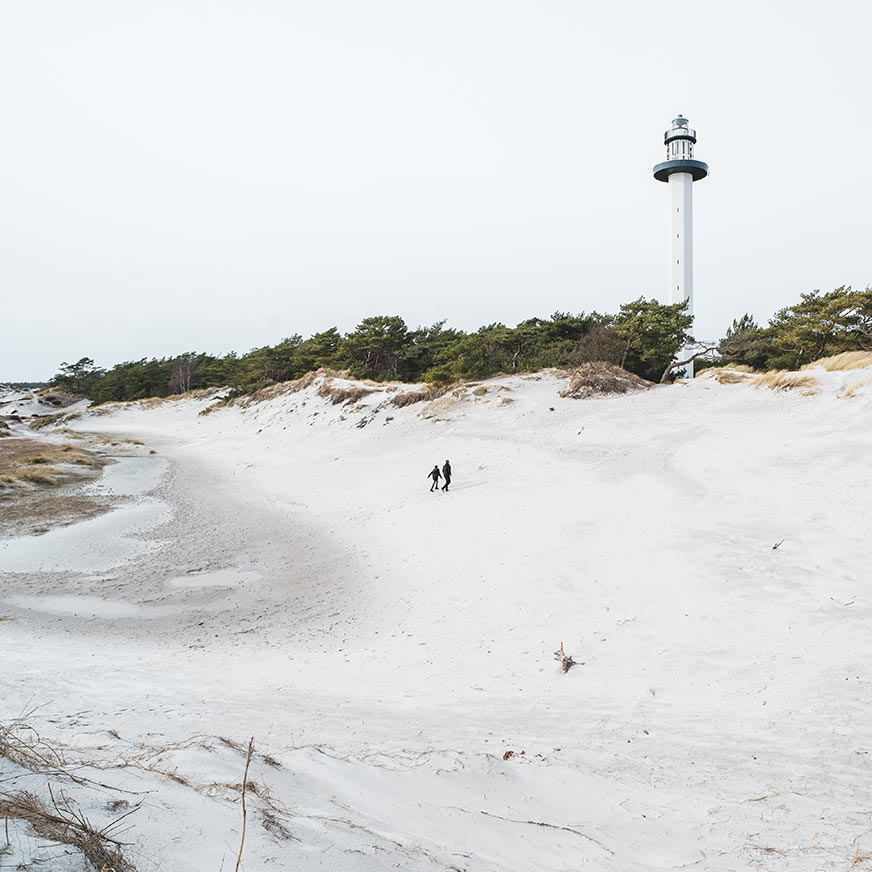 Two people walk on a white sand beach with a lighthouse in the background at Bornholm in Denmark