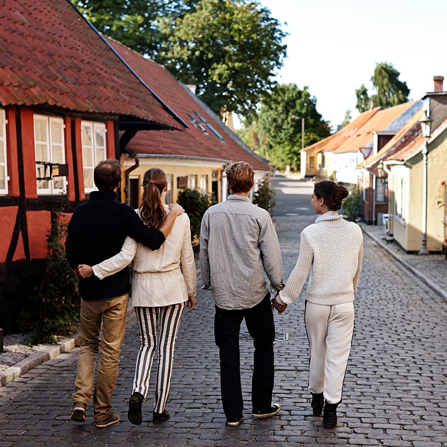 Two couples walk down a cobbled street next to colourful houses in Ærøskøbing town