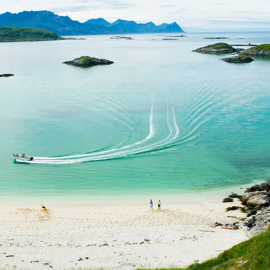 Boat in turquoise water at  Sommarøy with people standing on the nearby white sand beach.
