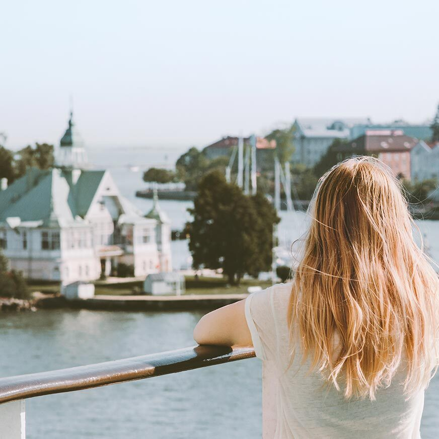 Woman facing away from the camera looks out onto the water and some buildings in a Finnish town